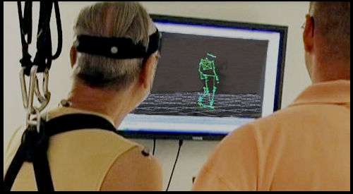 A participant and research looking at a computer showing a simulation of walking