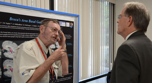 An investigator explaining research results to a man as they stand in front of a poster displaying information about the research